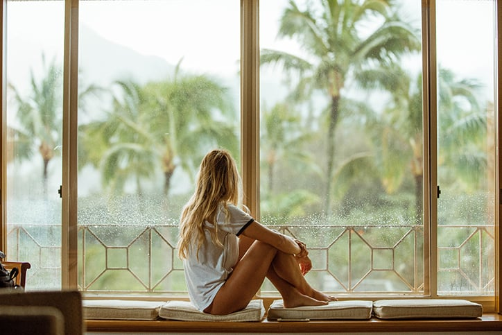 Girl sitting in house gazing out window at palm trees