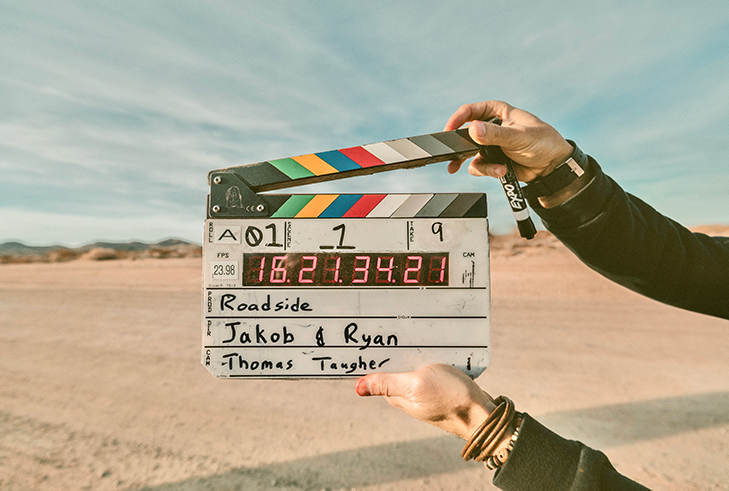 girl in leather jacket holding Film Clapper in the desert